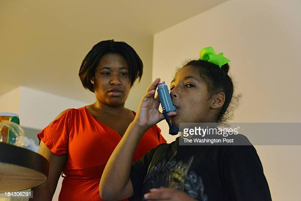 Jordyn Vincent R takes her asthma medicine albuterol under the watchful eye of her mother Carman Wilkins L at their home in DC east of the Anacostia...