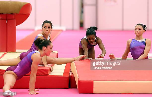 Jordyn Wieber Alexandra Raisman Gabrielle Douglas and Kyla Ross of the United States stretch after training sessions for artistic gymnastics ahead of...