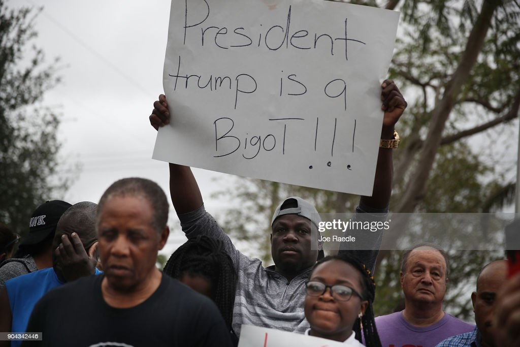 Jorel Francois holds a sign that reads, 'President trump is a Bigot!!!' as he joins with others to mark the 8th anniversary of the massive earthquake in Haiti and to condemn President Donald Trump's reported statement about immigrants from Haiti, Africa and El Salvador on January 12, 2018 in Miami, Florida. President Trump is reported to have called those places 'shithole countries' whose inhabitants are not desirable for U.S. immigration.