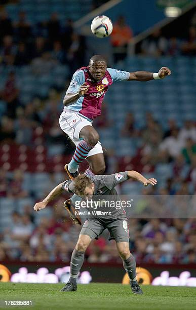Jores Okore of Aston Villa is challenged by Lee Frecklington of Rotherham United during the Capital One Cup Second Round match between Aston Villa...