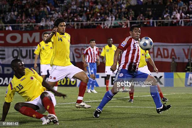 Jorge Achucarro of Paraguay vies for the ball with Cristian Zapata and Abel Aguilar of Colombia during their match as part of the 2010 FIFA World Cup...