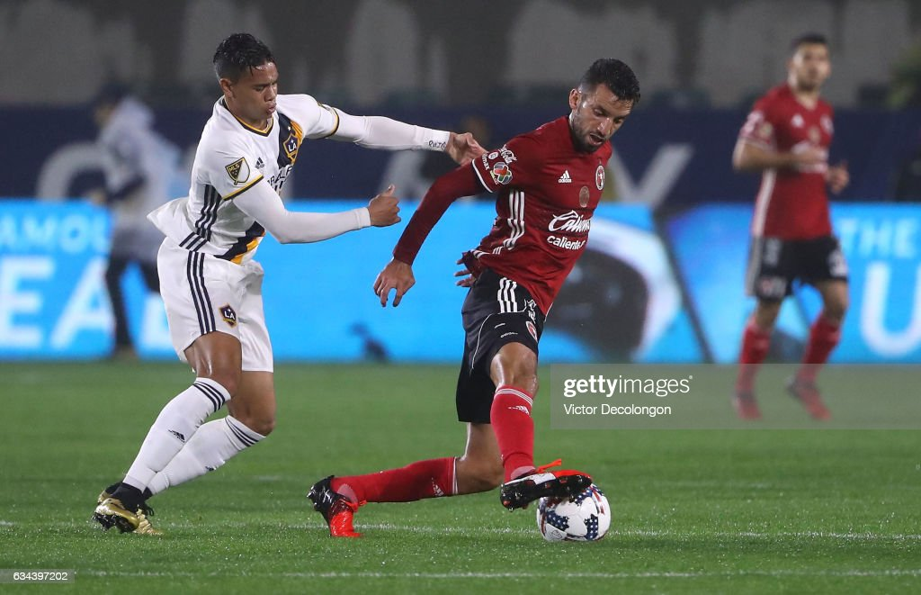 Jorge Alberto Ortiz #32 of Club Tijuana plays the ball from Ariel Lassiter #15 of the Los Angeles Galaxy during their friendly match at StubHub Center on February 7, 2017 in Carson, California.