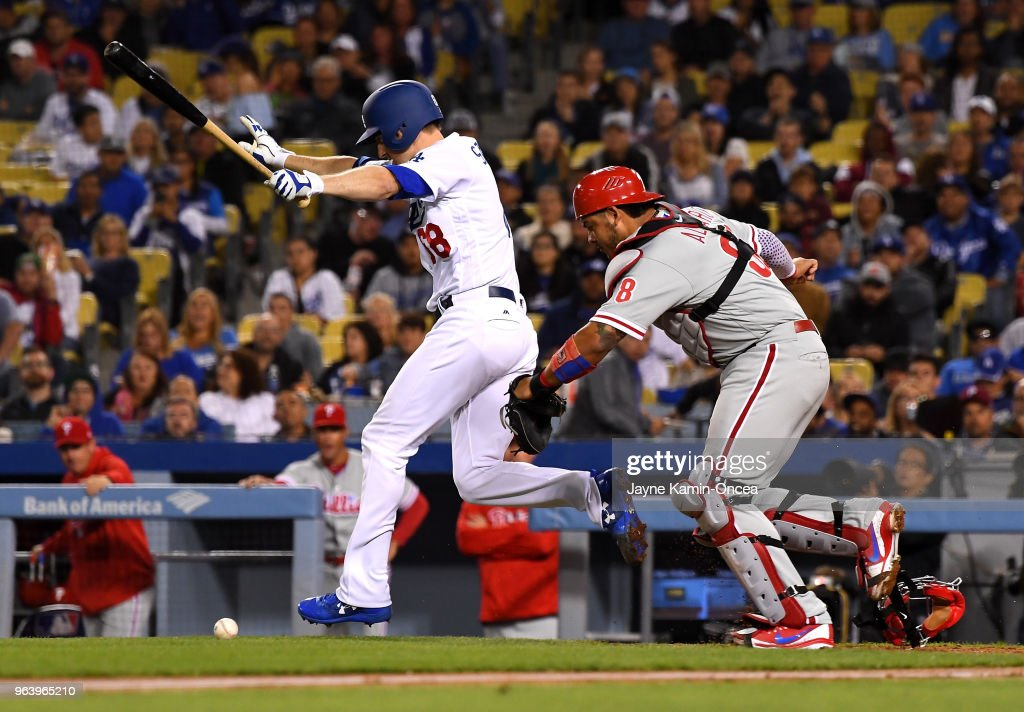 Jorge Alfaro #38 of the Philadelphia Phillies chases down the ball as Ross Stripling #68 of the Los Angeles Dodgers runs safely to first base on a bunt in the fourth at Dodger Stadium on May 30, 2018 in Los Angeles, California.