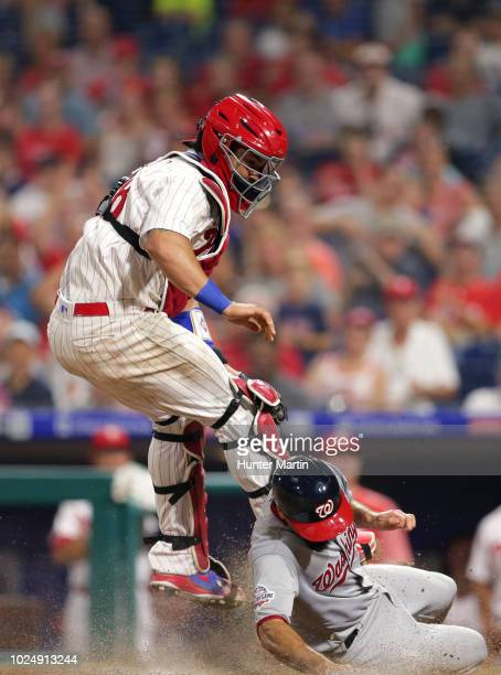 Jorge Alfaro of the Philadelphia Phillies leaps up to catch an errant throw as Anthony Rendon of the Washington Nationals slides safely into home...