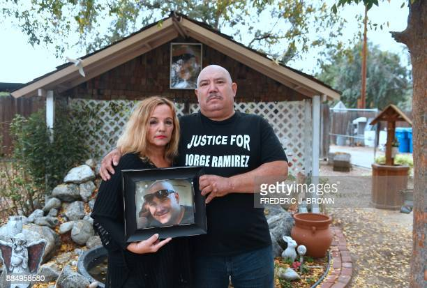 Jorge and Teresa Ramirez hold a portrait of their son Jorge Ramirez a former amateur boxing champion on November 17 2017 in front of a shrine at...