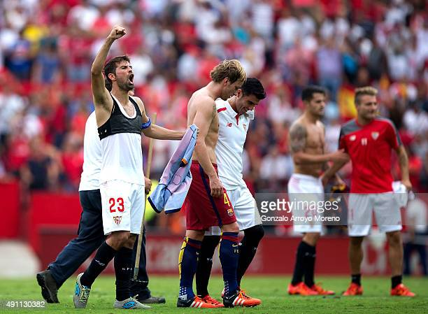 Jorge Andujar Moreno alias Coke of Sevilla FC celebrates their victory as his teammate Jose Antonio Reyes embraces Ivan Rakitic of FC Barcelona after...