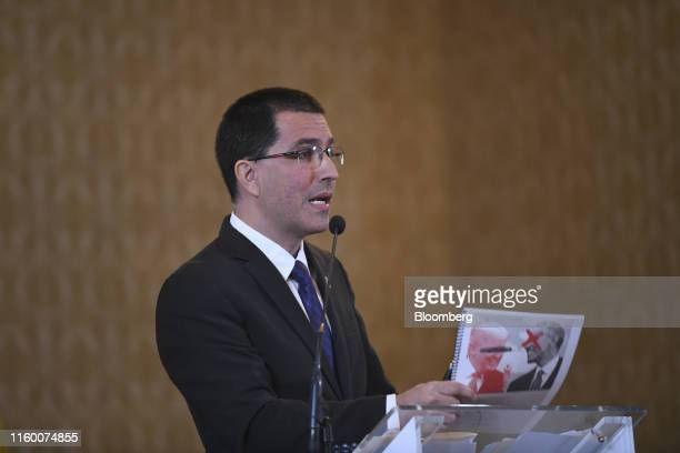Jorge Arreaza Venezuela's foreign minister speaks while holding a booklet displaying the images of US President Donald Trump and Barack Obama during...