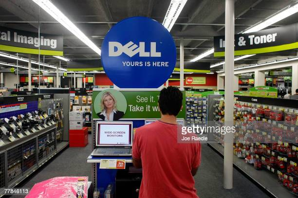 Jorge Bascha looks at a Dell computer on sale at a Staples store November 11 2007 in Miami Florida Dell Inc today began selling computers and...