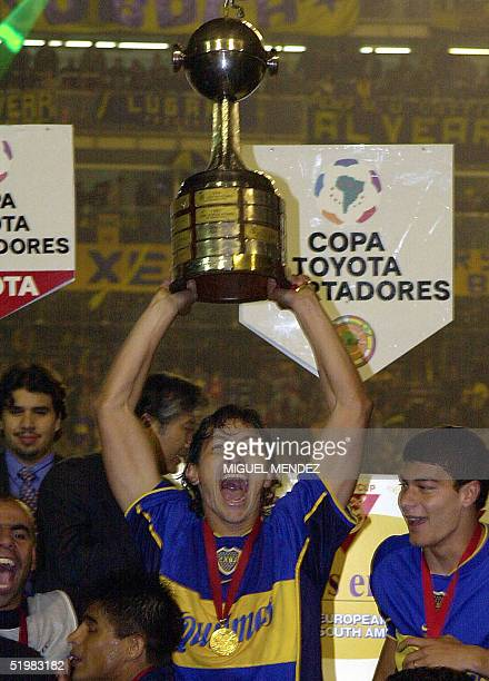 Jorge Bermudez captain of Argentina's Boca Juniors holds his team's trophy aloft after winning 31 over Mexico's Cruz Azul in the finals of the Copa...