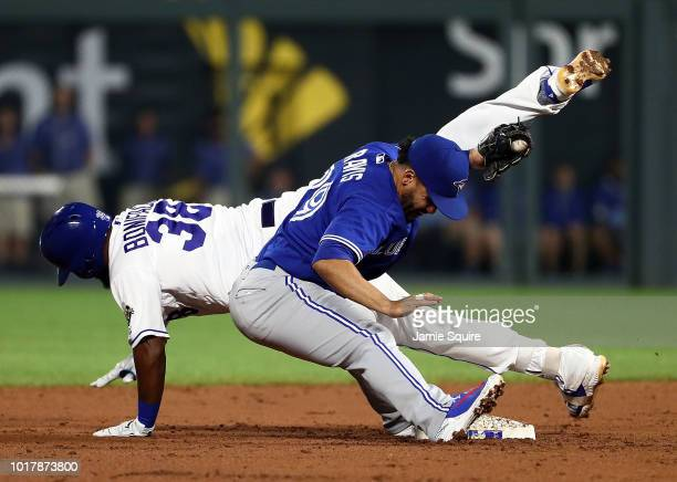 Jorge Bonifacio of the Kansas City Royals is tagged out by Devon Travis of the Toronto Blue Jays while attempting to turn a base hit into a double...
