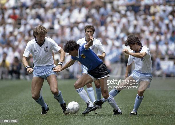 Jorge Burruchaga of Argentina in action against Steve Hodge and Terry Butcher of England during the World Cup QuarterFinal match between England and...
