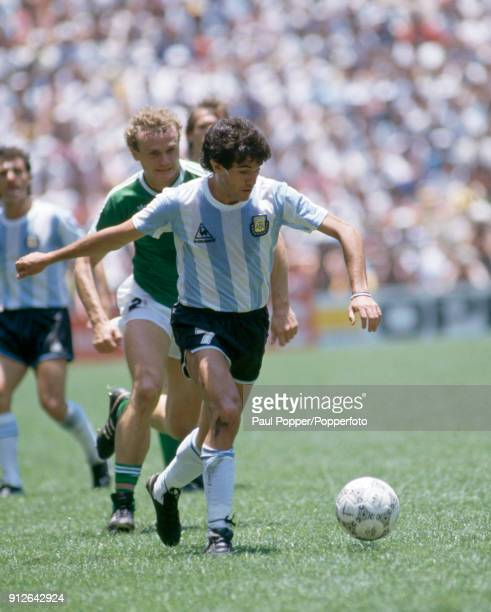 Jorge Burruchaga of Argentina is chased by Hans Peter Briegel of West Germany during the FIFA World Cup Final between Argentina and West Germany at...