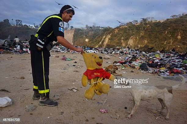 Jorge Chui the only fully qualified doctor and firefighter in the bomberos voluntarios struggles to pull away a stuffed animal from a stray dog in a...