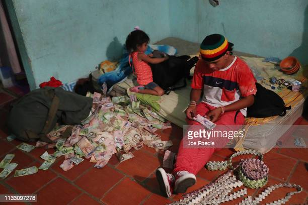 Jorge Corbero originally from Caracas Venezuela sits on his bed as he uses the Venezuela Bolívar to make items to sell on the street on March 1 2019...