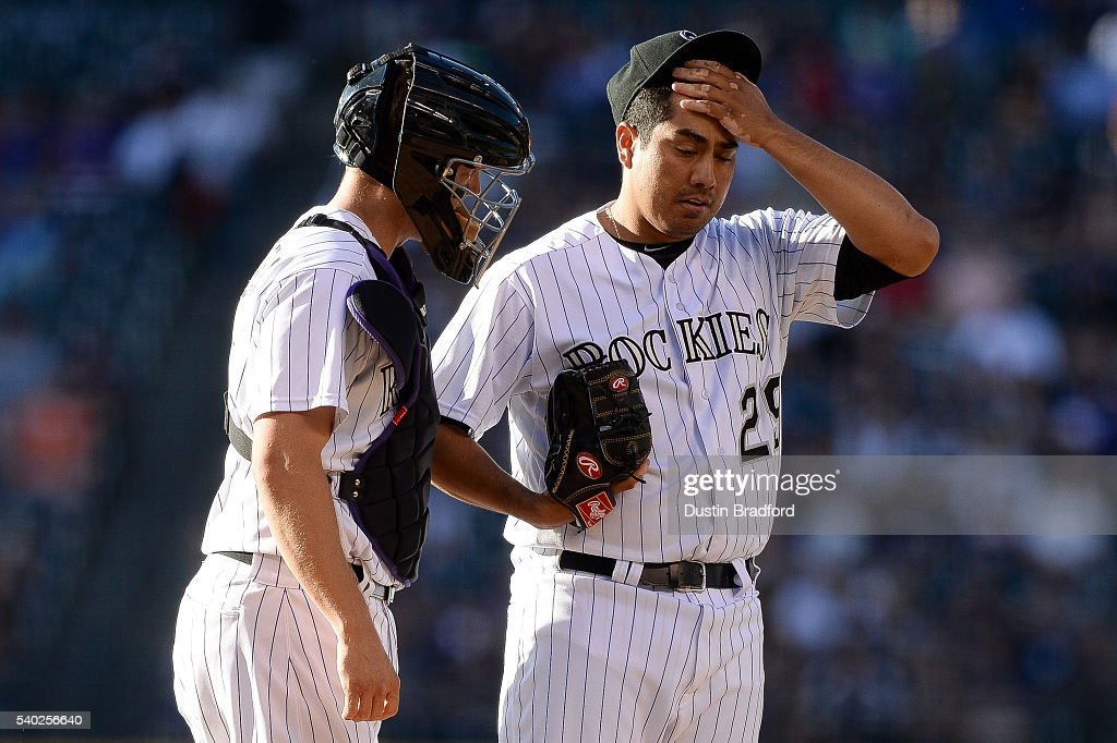 Jorge De La Rosa #29 of the Colorado Rockies rubs his brow and has a word with Nick Hundley #4 of the Colorado Rockies in the first inning during a regular season interleague game against the New York Yankees at Coors Field on June 14, 2016 in Denver, Colorado.