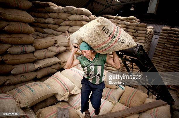 Jorge Eliecer Castaneda Ramos carries a 40kilo sack of coffee in a coop warehouse in Manizales Colombia on Saturday Oct 22 2011 Colombia the world's...