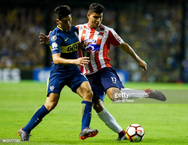 Jorge Enrique Arias de la Hoz of Junior fights for the ball with Cristian Espinosa of Boca Juniors during a group phase match between Boca Juniors...