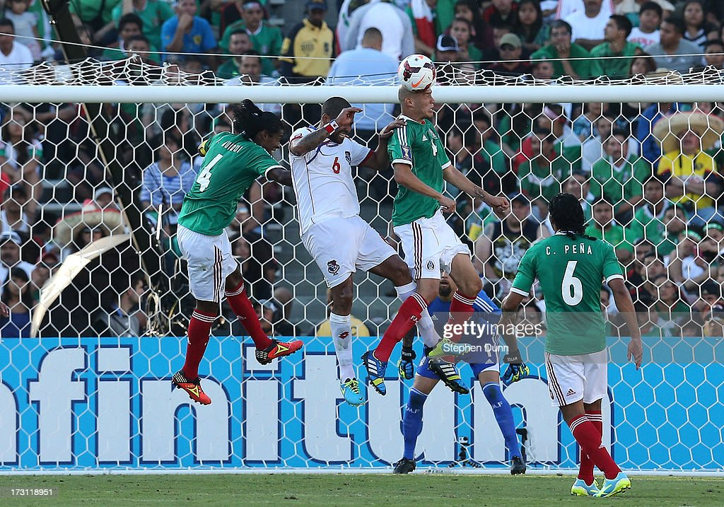 Jorge Enriquez #14 and Joel Huiqui #4 of Mexico jump for tha ball against Gabriel Gomez #6 of Panama during the first round of the 2013 CONCACAF Gold Cup at the Rose Bowl on July 7, 2013 in Pasadena, California. Panama won 2-1.