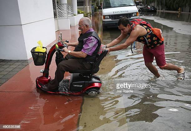 Jorge Florez pushes Antonio Romero out of a flooded street that was caused by the combination of the lunar orbit which caused seasonal high tides and...