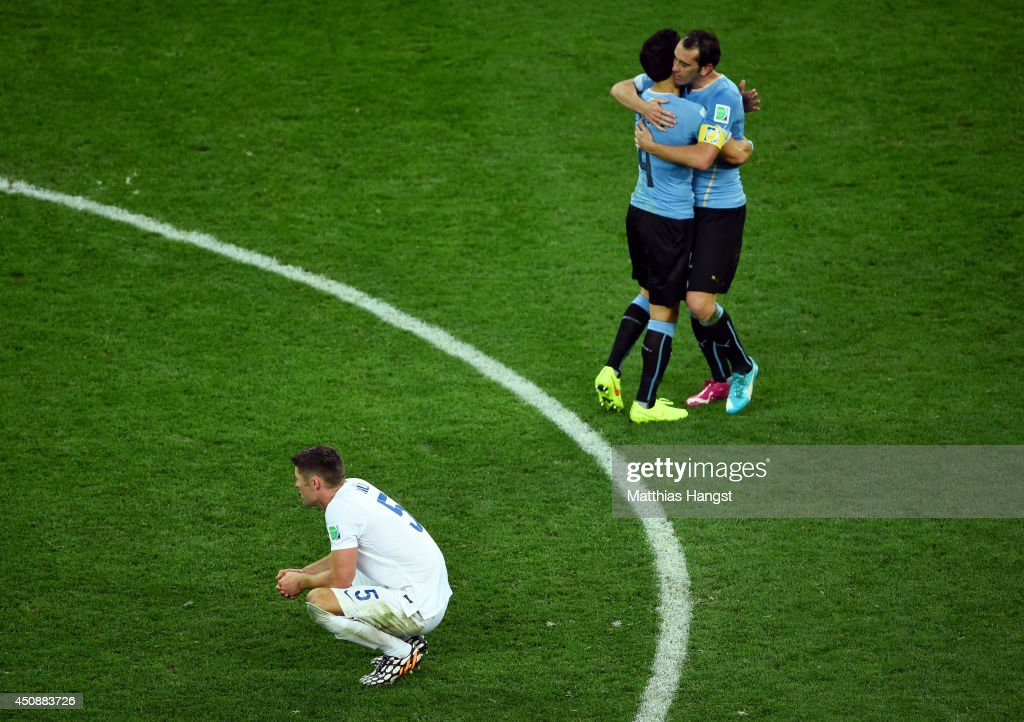 Jorge Fucile and Diego Godin of Uruguay hug as a dejected Gary Cahill of England looks on during the 2014 FIFA World Cup Brazil Group D match between Uruguay and England at Arena de Sao Paulo on June 19, 2014 in Sao Paulo, Brazil.