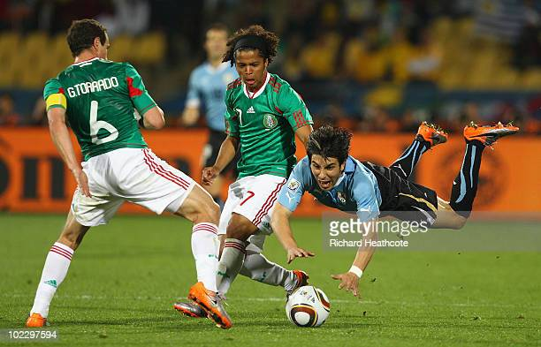 Jorge Fucile of Uruguay is tackled by Gerardo Torrado of Mexico during the 2010 FIFA World Cup South Africa Group A match between Mexico and Uruguay...