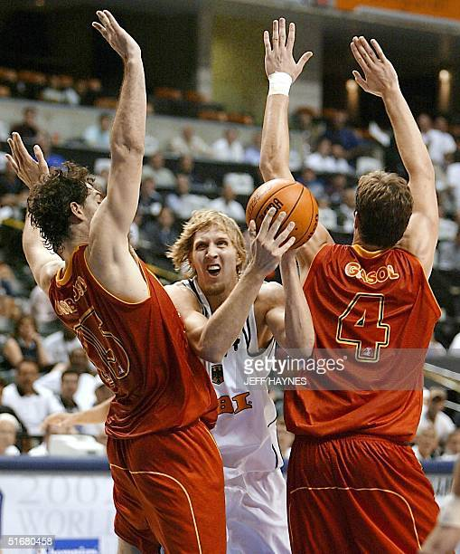 Jorge Garbajosa and Pau Gasol both of Spain guard Dirk Nowitzki of Germany 05 September 2002 during the second half of their quarter finals game of...