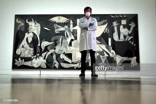 """Jorge Garcia Gomez-Tejedor, head of the restoration department, poses in front """"Guernica"""" by Spanish artist Pablo Picasso at the closed Reina Sofia..."""