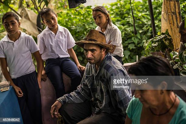 Jorge Graterol center who makes his living cutting eucalyptus for packages used in floral displays pauses during an interview at his home in...