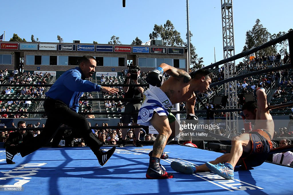 Jorge Lara (C) punches Fernando Montiel (L) knocking him down as referee Ray Corona (R) steps in during a featherweight fight at StubHub Center on April 30, 2016 in Carson, California.