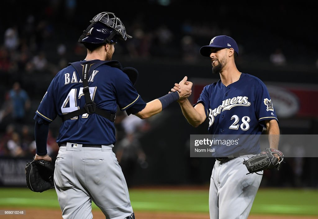 Jorge Lopez #28 and Jett Bandy #47 of the Milwaukee Brewers celebrate an 8-2 win against the Arizona Diamondbacks at Chase Field on May 16, 2018 in Phoenix, Arizona.