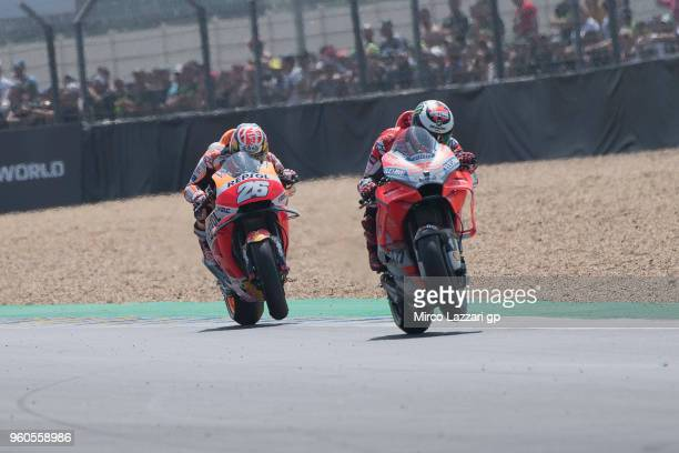 Jorge Lorenzo of Spain and Ducati Team and Dani Pedrosa of Spain and Repsol Honda Team lift the front wheel during the MotoGP race during the MotoGp...