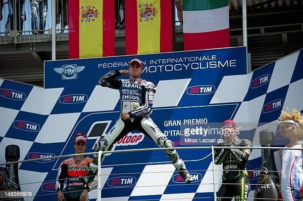 Jorge Lorenzo of Spain and Yamaha Factory Team celebrates the victory on the podium alongside Dani Pedrosa of Spain and Repsol Honda team and Andrea...