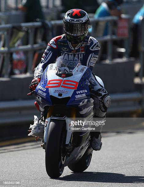 Jorge Lorenzo of Spain rider of the Yamaha Factory Racing Yamaha rides into pit lane after a seagull became caught in the front of his bike during...