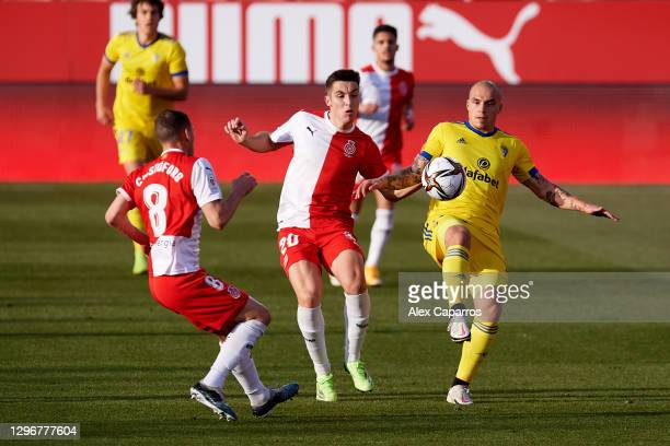 Jorge Marcos Pombo of Cadiz CF battles for possession with Sebastian Carlos Cristoforo and Valery Fernandez of Girona FC during the Copa del Rey...