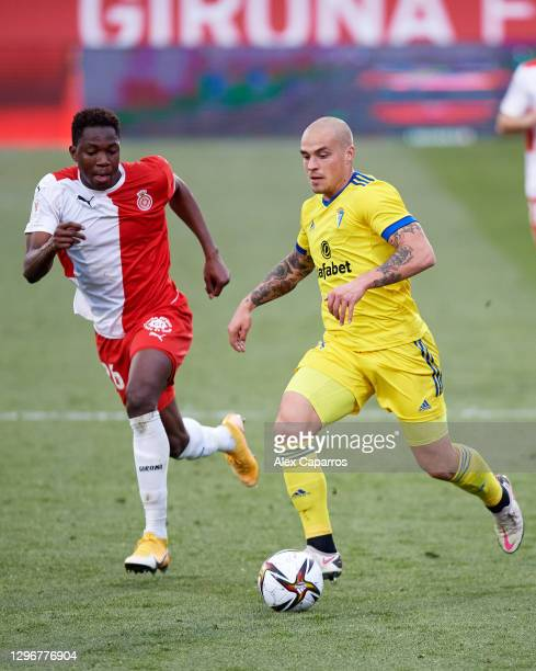 Jorge Marcos Pombo of Cadiz CF runs with the ball under pressure from Ibrahima Kebe of Girona FC during the Copa del Rey round of 32 match between...