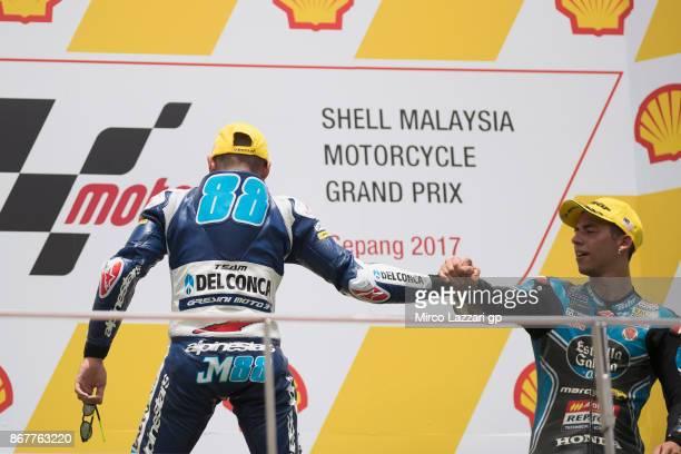 Jorge Martin of Spain and Del Conca Gresini Moto3 congratulates with Enea Bastianini of Italy and Estrella Galicia 00 on the podium at the end of the...