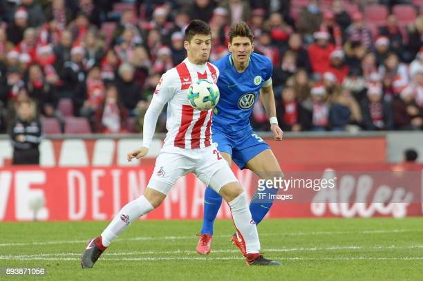 Jorge Mere of Koeln and Mario Gomez of Wolfsburg battle for the ball during the Bundesliga match between 1 FC Koeln and VfL Wolfsburg at...