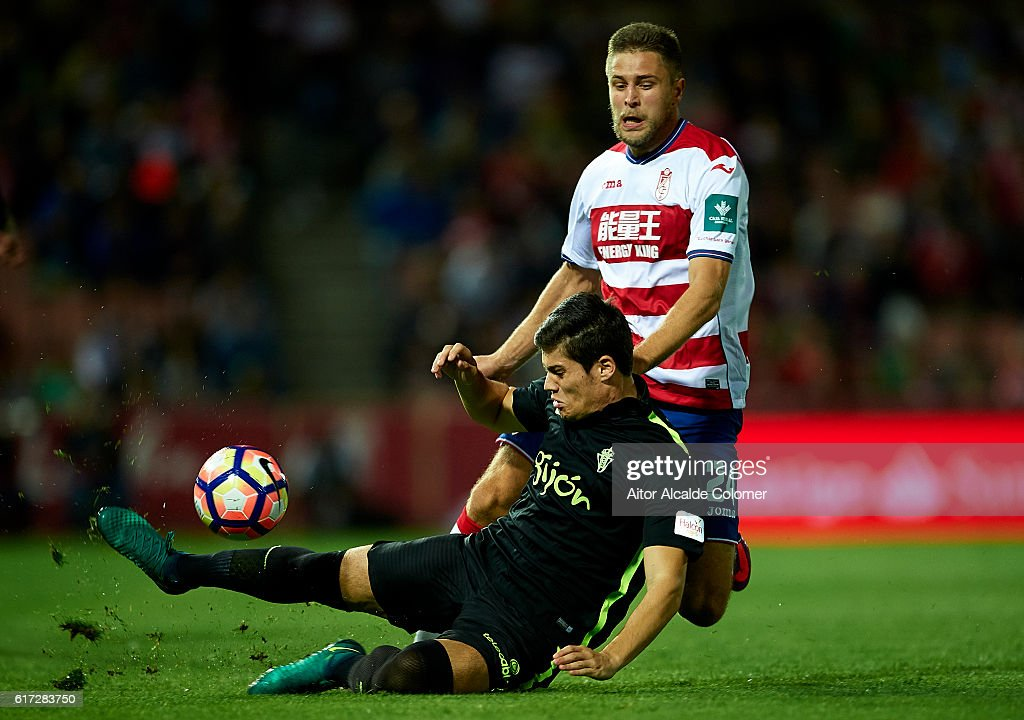 Jorge Mere of Sporting Gijon (R) competes for the ball with Artem Anatoliovich Kravets of Granada CF (L) during the match between Granada CF vs Sporting Gijon as part of La Liga at Nuevo los Carmenes Stadium on October 22, 2016 in Granada, Spain.