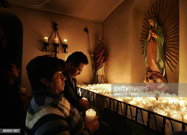 Jorge Merida far left Manuel Cortes and wife Ofelia Merida middle pray and light candles to honor the Virgin de Guadalupe whos statue is at right...