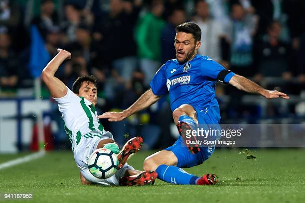 Jorge Molina of Getafe competes for the ball with Aissa Mandi of Real Betis during the La Liga match between Getafe and Real Betis at Coliseum...