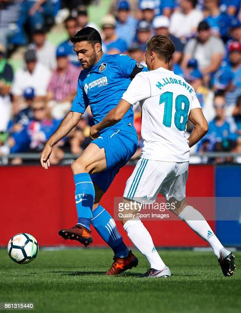 Jorge Molina of Getafe competes for the ball with Marcos Llorente of Real Madrid during the La Liga match between Getafe and Real Madrid at Estadio...