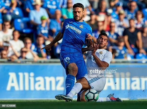 Jorge Molina of Getafe is tackled by Theo Hernandez of Real Madrid during the La Liga match between Getafe and Real Madrid at Estadio Coliseum...