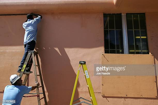 Jorge Navarro and Lanard Chester cover a window with plywood as they prepare the building for the approaching Tropical Storm Ernesto that is...