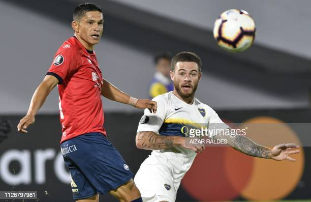 Jorge Ortiz of Bolivia's Wilstermann vies for the ball with Julio Buffarini of Argentina's Boca Juniors during their Copa Libertadores football match...