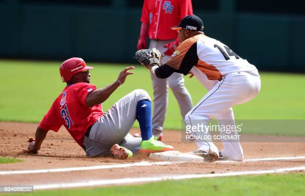 Jorge Padilla of Criollos de Caguas from Puerto Rico slides safe in first base during a Caribbean Baseball Series match against Aguilas del Zulia of...