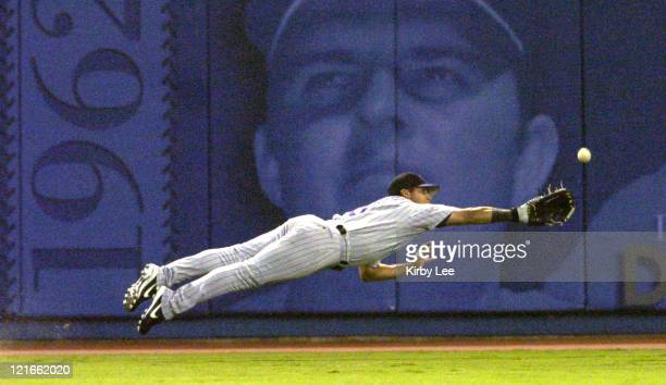 Jorge Piedra of the Colorado Rockies dives for a fly ball by Cesar Izturis of the Los Angeles Dodgers in the first inning of 87 loss at Dodger...