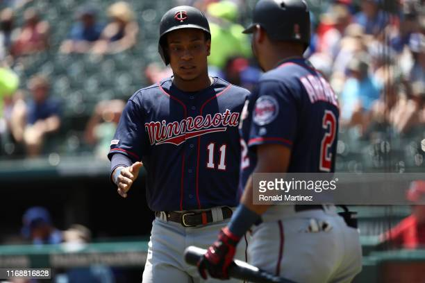 Jorge Polanco of the Minnesota Twins celebrates a run with Luis Arraez in the first inning against the Texas Rangers at Globe Life Park in Arlington...