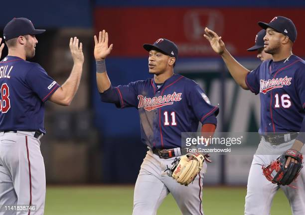 Jorge Polanco of the Minnesota Twins celebrates a victory with Matt Magill and Jonathan Schoop against the Toronto Blue Jays at Rogers Centre on May...