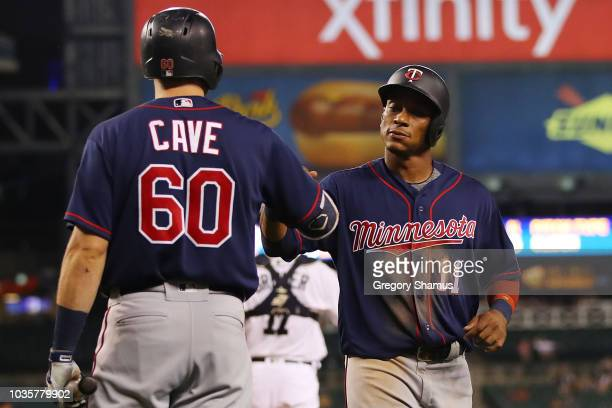 Jorge Polanco of the Minnesota Twins celebrates scoring a sixth inning run with Jake Cave while playing the Detroit Tigers at Comerica Park on...