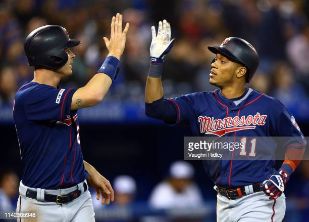 Jorge Polanco of the Minnesota Twins high fives Max Kepler after hitting a tworun home run in the second inning during a MLB game against the Toronto...